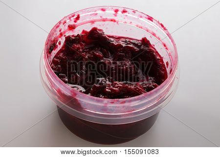 Black currant jam in the round plastic container on white background
