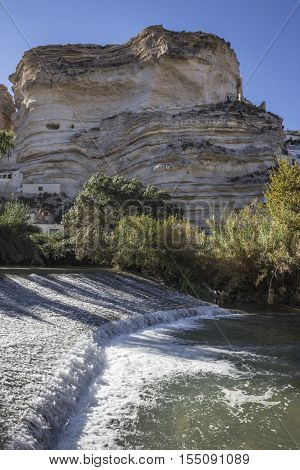 Alcala del Jucar Spain - October 29 2016: Clear waters of the river Jucar on the Roman bridge Castle of Almohad origin of the century XII take in Alcala of the Jucar Albacete province Spain
