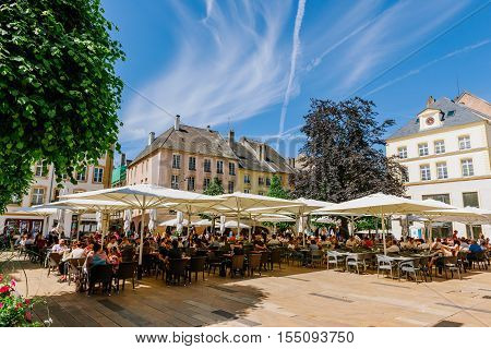 THIONVILLE FRANCE - JUNE 10 2016: Full cafe beer restaurant terrace in center of old french city of Thionville France with couples friends and families drinking eating surrounded by green trees and beautiful blue sky