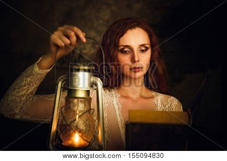 Beautiful red-haired young woman with kerosene lamp reading a book