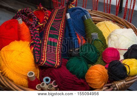 Crafts. Basket with colored woolen threads and hand-woven belt. Image suitable for background.