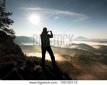 Man Takes Photos With Phone On Rock Empire. Dreamy Fogy Mountains,