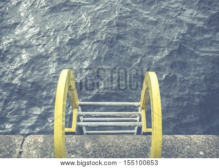 Conceptual Image Of A Yellow Ladder Into Blue Ocean Water At A Harbor