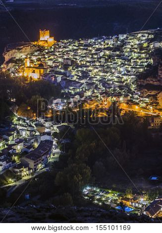 Alcala del Jucar Spain - October 29 2016: Night view of the city on top of limestone mountain is situated Castle of the 12TH century Almohad origin take in Alcala of the Jucar Albacete province Spain