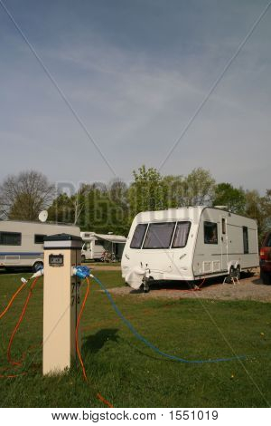 Caravans parked with electric hook-up at a campsite poster