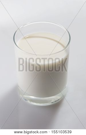 Colorless glass full of cow milk on white background