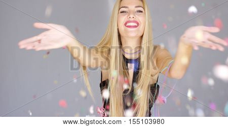 Sexy, blond girl blowing confetti to camera direction