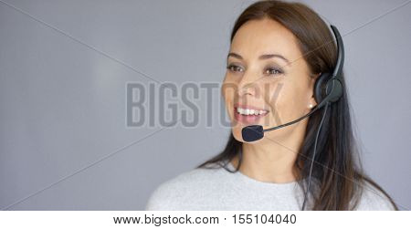 Adorable call center agent speaking with someone on headset