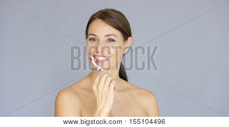 Attractive smiling woman brushing her teeth