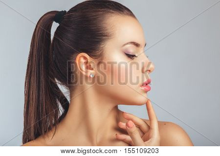 Beautiful Spa Woman Touching her ckin. Youth and Skin Care Concept. Beautiful girl after a shower with wet hair and clean skin. Natural beauty. Sensual and Fresh