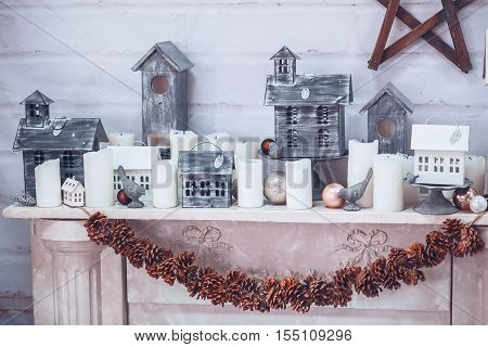 Christmas and New Year decorated background.Christmas decorations with houses birds candles balls and pine cones on a wooden background