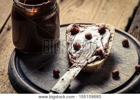 Nutella on the sandwich for breakfast on old wooden table