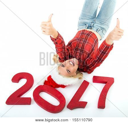 Charming smiling young beautiful blond model lying over white background near numbers 2017. Christmas girl. New Year 2017 woman with thumbs up.
