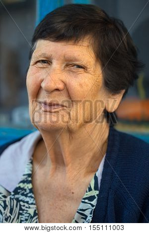 portrait of smiling grandma sitting outdoors close up