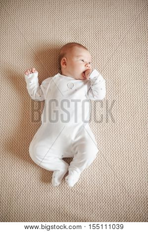 Pretty baby in a white pajamas lying on his back. Flat lay