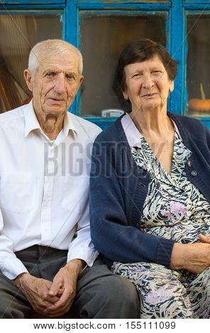 portrait of smiling grandparents sitting outdoors close up