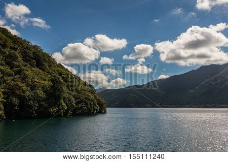 Lake Ashi Japan - September 27 2016: Forested slopes descend into the tranquil water of the lake under a blue sky dotted by smaller white clouds. Light reflected on parts of the water.