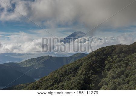 Hakone Japan - September 27 2016: The summit of mount Fuji visible and encircled by bands of clouds as it is seen from Mount Komagatake. Forested hills in foreground valley in distance.