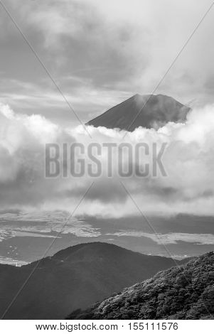 Hakone Japan - September 27 2016: Black and white portrait of the summit of mount Fuji visible and encircled by bands of clouds as it is seen from Mount Komagatake. Valley in foreground.