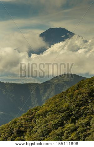 Hakone Japan - September 27 2016: Portrait of the summit of mount Fuji visible and encircled by bands of clouds as it is seen from Mount Komagatake. Valley and forest in foreground.