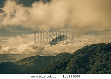 Hakone Japan - September 27 2016: Summit of mount Fuji visible and encircled by bands of dark rainy storm clouds as it is seen from Mount Komagatake. Valley and forest in foreground.