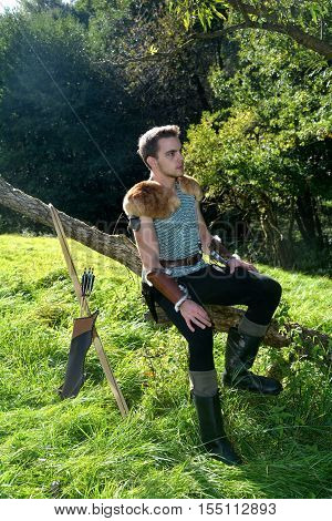 Young Medieval dressed man, sits on branch, arms on legs and looks aside, arrow and curve stands besides