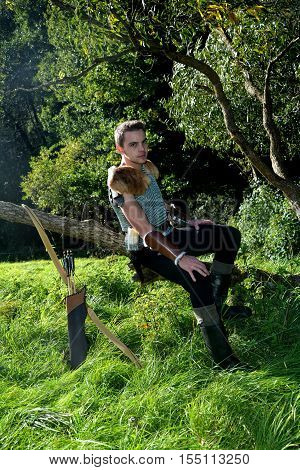 Young Medieval dressed man, sits on branch, hands on legs and looks forwards, arrow and curve stands besides