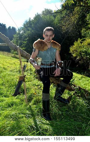 Young medieval archer with chain shirt sits on branch in the nature in the sunlight, drinking horn in the hand,  looks down ,arrow and curve stands besides