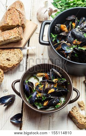 Cooked mussels with garlic and parsley on old wooden table
