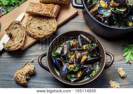 Homemade mussels with garlic and parsley on old wooden table
