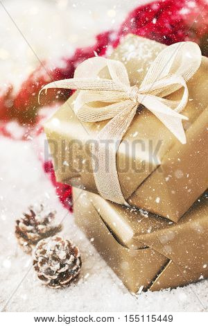 Christmas presents or gifts with elegant bow and christmas decorations on bright snowy background christmas concept toned