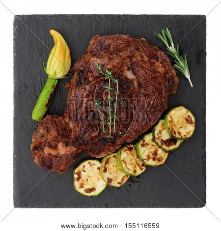 Rib-eye steak with vegetables on black slate plate, isolated on white