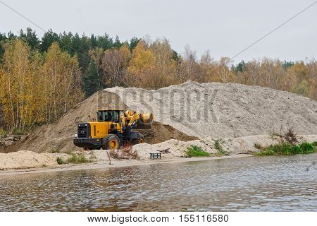 Earth-mover and a large pile of bank sand