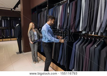 Handsome Business Man And Woman Fashion Shop, Customers Choosing Suit Clothes In Retail Store Young People Shopping Formal Wear