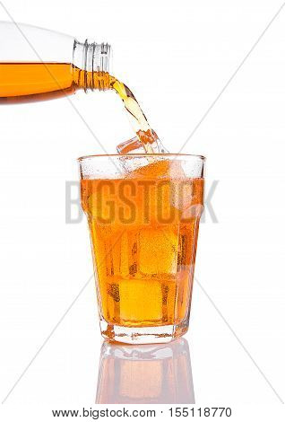 Pouring orange energy soda drink in glass with ice on white background