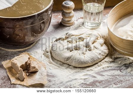 Preparing homemade pizza dough on old wooden table