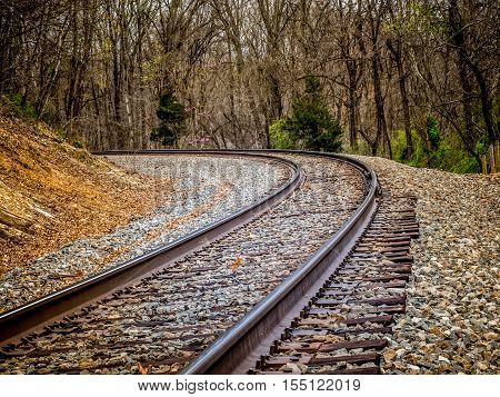 Railroad tracks through a forested countryside and around a curve
