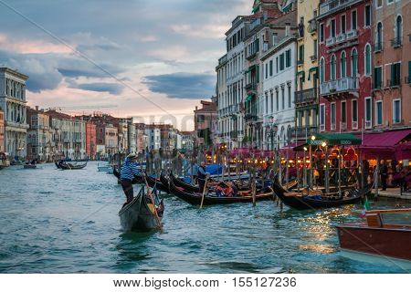Gondolier floating near restaurants in Venice, Italy