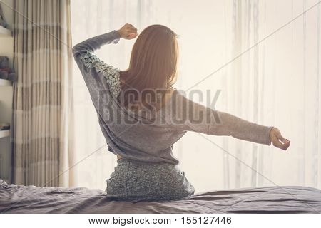 Woman stretching arms and waking up sitting on the bed in the morning at home