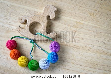 Necklace Made From Knitted Beads And Wooden Horse Toy For The Baby Sitting In A Sling. Knitted Beads