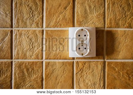 White electric socket on kitchen wall with ceramic tiles pattern texture