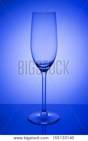 Glass for champagne, empty. On a blue background, on a gleam. Has specular reflection of the lower part