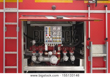 Devices on the control panel of the fire truck of red color, the back door is open up. On each side from a door there are ladders