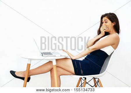Young beautiful Caucasian woman covering mouth with surprise and speechless look while sitting on white desk over white isolated background with copy space
