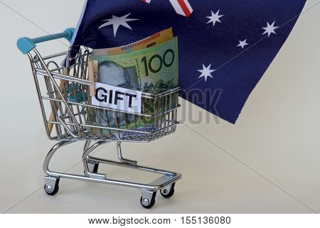 Australian dollar notes and flag in a trolley as a gift.