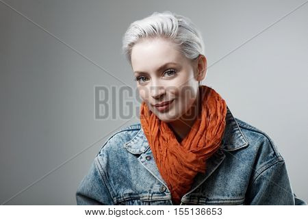 Studio portrait of casual young woman in denim jacket, smiling.