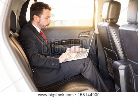 Businessman Using Laptop In A Car