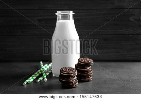 Chocolate cookies, straws and bottle of milk on dark table