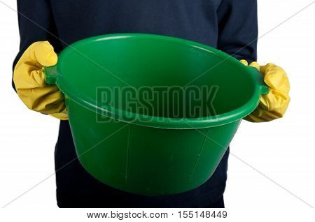 Human in dark-blue shirt and rubber gloves holds small green washbowl. Isolated on white