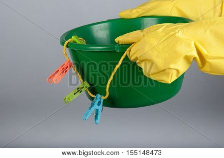Hands in yellow rubber gloves hold small green washbowl with colored clothespins and clothline